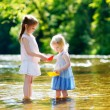 Two little sisters  with paper boats — Stock Photo #66731833