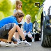 Father and daughters  changing a car wheel — Stock Photo
