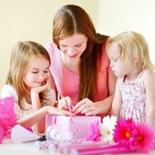 Mother and daughters wrapping gift — Stock Photo