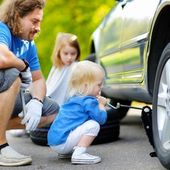 Little girl helping father with car — Stockfoto