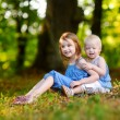 Little sisters sitting on grass — Stock Photo #68759739