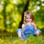 Little girl sitting in green grass — Stock Photo #68759951