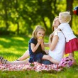 Mother and daughters having picnic in park — Stock Photo #68759973