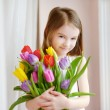 Little girl with colorful tulips — Stock Photo #68760041