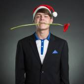 Man with a flower and cap of Santa Claus. — Stock Photo