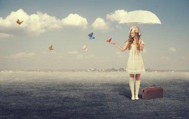 Girl with umbrella catching butterflies.