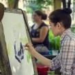 Young woman painting outdoors. — Stock Photo #76877095