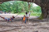 Thai people having a rest under shadow of old tree near Kata beach on Phuket, Thailand — Foto de Stock