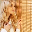 Young happy woman looking out the window through the blinds — Stock Photo #65220593