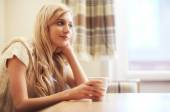 Young blonde woman with coffee cup at the table — Stock Photo