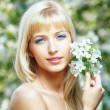 Beautiful blonde with flowers — Stock Photo #72528209