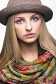 Studio portrait of young woman in hat — Stock Photo