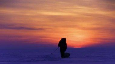 Man go to sunset on snow desert — Stock Video