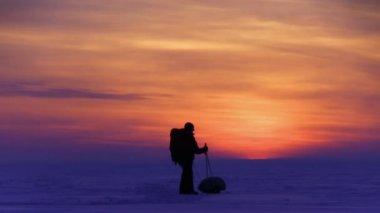 夕暮れ時の雪の砂漠で男 — ストックビデオ