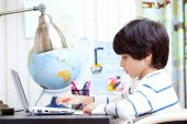 Schoolchild working on a computer — Stock Photo
