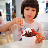 Boy eating ice cream with chocolate and strawberries — Stock Photo