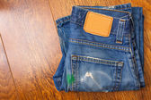 Old blue jeans with brown label on the belt smeared with green p — Foto de Stock