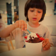 Boy eating ice cream with chocolate and strawberries — Stock Photo #61882331