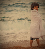 Boy wrapped in a towel on the beach — Stock Photo