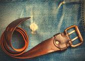 Vintage belt on old blue jeans — Stock Photo