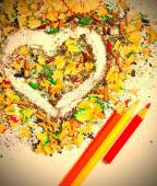 Heart, three pencils and varicolored wooden shavings — Stock Photo