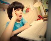 Surprised boy looking at a computer monitor — Stock Photo