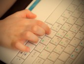 Child's hand on the laptop keyboard — Stock Photo