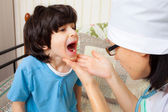Doctor looks throat of boy — Stock Photo