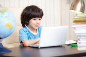 Smiling boy looking at a computer monitor — Stock Photo