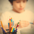 Colored pencils for drawing in pencil holders and the child on b — Stock Photo #70745989