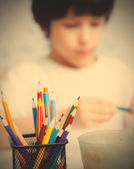 Colored pencils for drawing in pencil holders and the child on b — Stock Photo