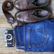Still life with blue jeans, brown boots, leather belt and camera — Stock Photo #72196919