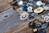 Old buttons in large numbers scattered on aged wooden boards — Stock Photo