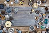 Set of vintage buttons on aged wooden boards — Stock Photo