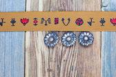 Vintage tape with embroidered ornaments and old buttons — Stock Photo