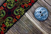 Old band with embroidered ornaments and vintage button — Stock Photo