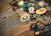 Old buttons in large numbers scattered on aged wooden boards — Foto Stock