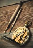 Reverse side of the vintage pocket watch and a screwdriver — Stock Photo