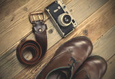 Sturdy brown boots, leather belt, and rangefinder camera — Stock Photo