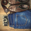 Still life with blue jeans, brown boots, leather belt and camera — Stock Photo #73980965