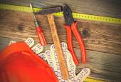 Vintage pliers, hammer, screwdriver, tape measure, a bright helm — Stock Photo