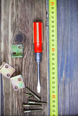 Vintage screwdriver, screws, angles and measuring tape — Stock Photo