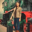 Adult woman traveler with a suitcase near the vintage steam loco — Stock Photo #76059071