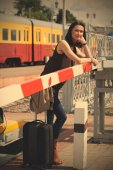 Woman traveler with a suitcase near the railway barrier — Stock Photo