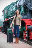 Adult woman traveler with a suitcase near the vintage steam loco — Stock Photo