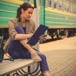 Beautiful woman traveler taking notes in a notebook — Stock Photo #77612466