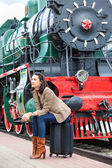 Pretty woman sitting on a suitcase on railroad station — Stock Photo
