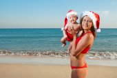 Woman and baby in santa hat on sea — Stock Photo