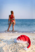 Sexy woman in santa hat on sea — Stok fotoğraf