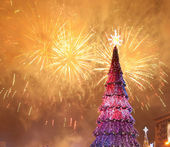 Christmas tree and fireworks — Stock Photo